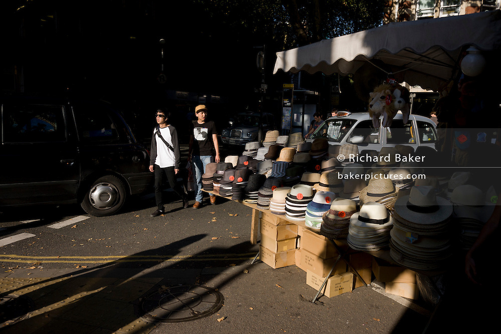Young men pass alongside a hat market stall, one wearing a modern baseball cap instead of a trilby on sale.