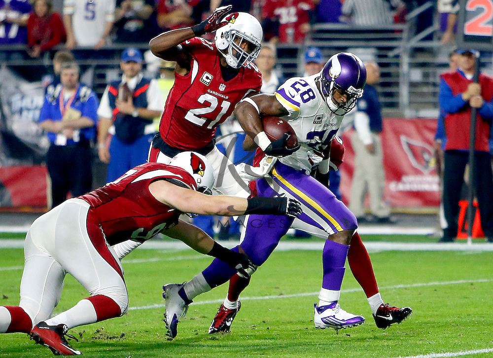 Minnesota Vikings running back Adrian Peterson (28) breaks free from Arizona Cardinals free safety Rashad Johnson, right, cornerback Patrick Peterson (21), and tackle Josh Mauro, left, during the first half of an NFL football game, Thursday, Dec. 10, 2015, in Glendale, Ariz. (AP Photo/Rick Scuteri)