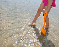 Girl (10-12) with toy spade in shallow water low section