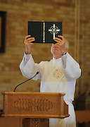 A permanent deacon raises the lectionary during Mass.
