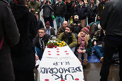 "London, February 14th 2015. A few dozen activists from Occupy Democracy gather at Parliament Sqyuuare to hold a vigil and funeral for British democracy, which they say has been killed by Parliaments apparent alliance with corporates at the expense of the ""99%"".  PICTURED: A coffin forms the centrepiece of the protest as speakers address the gathering.  // Photographer contact for payment details if not already on record: Tel 07966016 296, email paul@pau;ldaveycreative.co.uk."