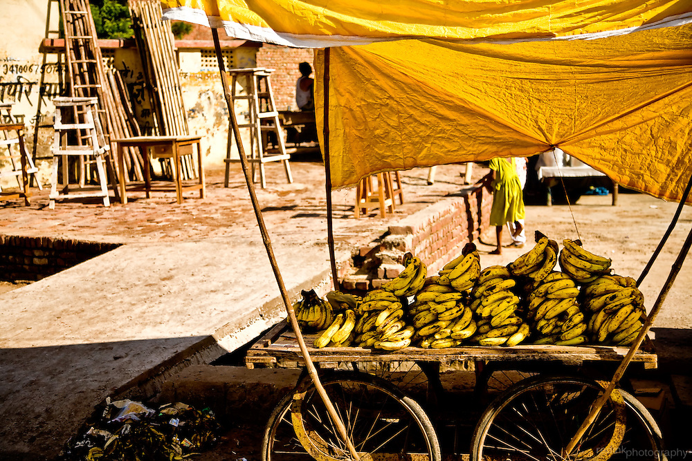 Banana cart on the streets of India. Bright yellow tarp over the cart, construction in the background.