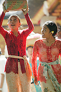 Two young Indonesian girls return from ceremony in traditional clothing in Bali