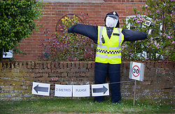 © Licensed to London News Pictures. 27/04/2020. Capel, UK. A scarecrow depiction of a police officer stands at the front of a house in the Surrey village of Capel. Residents of the village have resurrected their summer tradition of scarecrows in tribute to NHS medical staff and other key workers. Up to 30 of the life size home made doll like characters can be seen in front gardens throughout the village. The public have been told they can only leave their homes when absolutely essential, in an attempt to fight the spread of coronavirus COVID-19 disease. Photo credit: Peter Macdiarmid/LNP