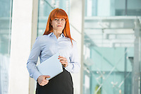 Confident businesswoman looking away while holding laptop in office