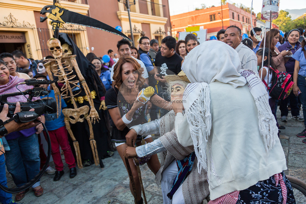 A television reporter interviews a costumed character during the Day of the Dead Festival known in spanish as Día de Muertos on October 25, 2013 in Oaxaca, Mexico.
