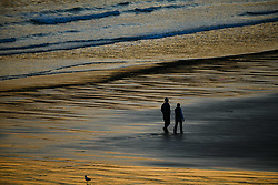 © Licensed to London News Pictures. 13/09/2020. Swansea, UK. A couple enjoy a walk along Caswell Bay in Gower as the sunsets, on a beautiful evening in south Wales. The UK enjoyed a fine weekend of warm and sunny weather. Photo credit: Robert Melen/LNP