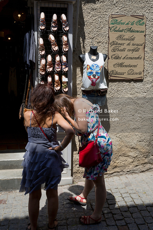 Young women try on sandals outside a footwear shop, on 27th May, 2017, in Carcasonne, Languedoc-Rousillon, south of France. Situated on the right bank of the Aude, the City, a medieval village that is still inhabited, has 52 towers and two concentric walls totalling 3 km in length.