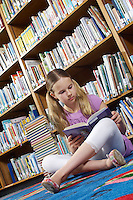 Girl sitting on the floor and reading book in library, tilt