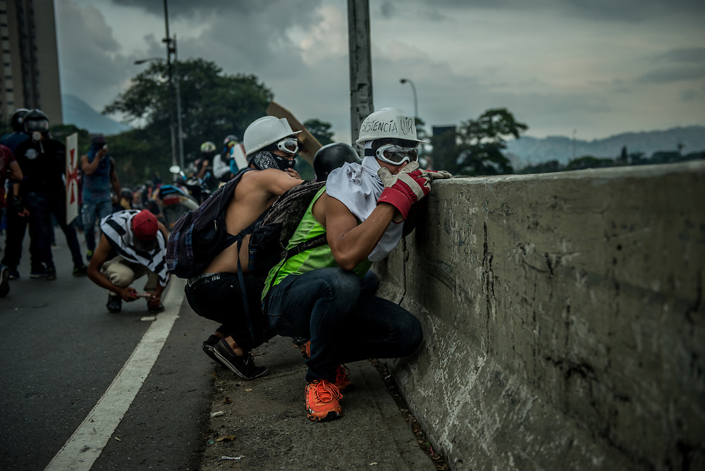 CARACAS, VENEZUELA - MAY 10, 2017:  Anti-government protesters take cover from rubber bullets and buckshot being shot at them as they fight to take control of Francisco Fajardo highway from National Guard soldiers. The streets of Caracas and other cities across Venezuela have been filled with tens of thousands of demonstrators for nearly 100 days of massive protests, held since April 1st. Protesters are enraged at the government for becoming an increasingly repressive, authoritarian regime that has delayed elections, used armed government loyalist to threaten dissidents, called for the Constitution to be re-written to favor them, jailed and tortured protesters and members of the political opposition, and whose corruption and failed economic policy has caused the current economic crisis that has led to widespread food and medicine shortages across the country.  Independent local media report nearly 100 people have been killed during protests and protest-related riots and looting.  The government currently only officially reports 75 deaths.  Over 2,000 people have been injured, and over 3,000 protesters have been detained by authorities.  PHOTO: Meridith Kohut