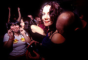 A pretty girl acting as a head rest in the middle of a crowded club, UK 2000's