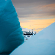 An Antarctic cruise ship in the distance seen through icebergs, as the setting sun casts a golden glow on the horizon.