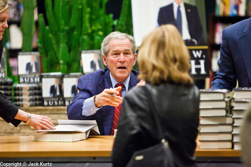 """09 DECEMBER 2010 - PHOENIX, AZ: Former President GEORGE W. BUSH greets people and signs copies of his book, """"Decision Points"""" at the Barnes & Noble Bookstore in Phoenix, AZ, Thursday, Dec. 9. More than 2,000 people lined up starting at 5AM to get copies of the former President's book, """"Decision Points."""" A handful of protesters demonstrated against President Bush near the bookstore, calling him a """"war criminal.""""   PHOTO BY JACK KURTZ"""