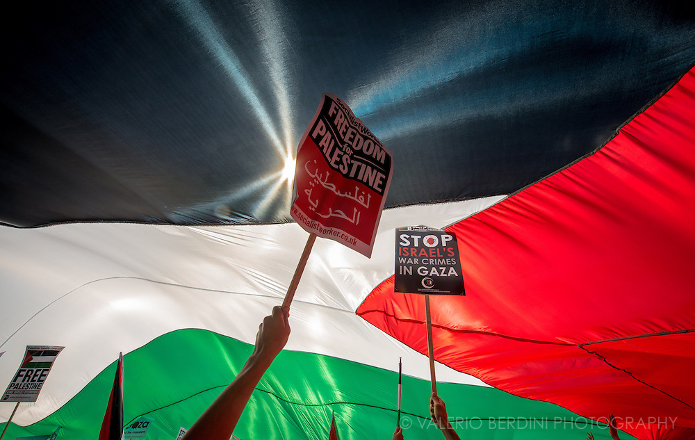 Placards hold a huge Palestinian flag. Stop the massacre in Gaza. 150.000 thousands people march in the streets of Central London to Hyde Park ask the end of Israeli invasion of Gaza. 9 August 2014