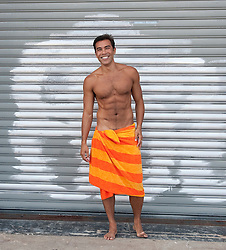 Asian American Man In A Towel Smiling While Standing By A graffiti Gated Storefront