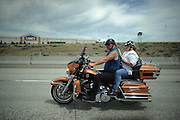 A couple ride an orange motorcycle on the highway together outside a Lowe's store. She is reading a book while riding behind her husband.