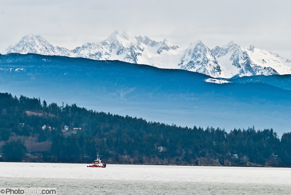 A tugboat cruises Rosario Strait (the Salish Sea) beneath Twin Sisters Mountain in Mount Baker Wilderness. Seen on Washington State Ferries, San Juan Islands route, USA.