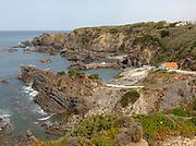 Rocky rugged coastline near fishing port village of Azenha do Mar,  Alentejo Littoral, Portugal, southern Europe