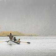 An angler in a drift boat fly fishes for trout as a golden retriever looks on; South Fork of the Snake River, Idaho.