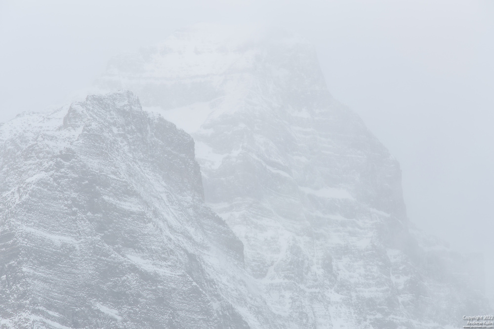 Telephoto closeup of the snow-covered and squall-enshrouded mountaintops of  Haddo Peak (background) and Mount Sheol (foreground) near Lake Louise in Banff National Park, Canada.
