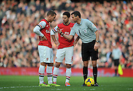 Referee Andre Marriner talks to Arsenal's Lukas Podolski  during Barclays Premier League , Arsenal v Sunderland at the Emirates Stadium in London, England on Saturday 22nd Feb 2014.<br /> pic by John Fletcher, Andrew Orchard sports photography.