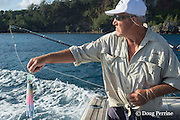 deckhand Walter Morehead out fishing lure on charter boat Reel Addiction, Vava'u, Kingdom of Tonga, South Pacific