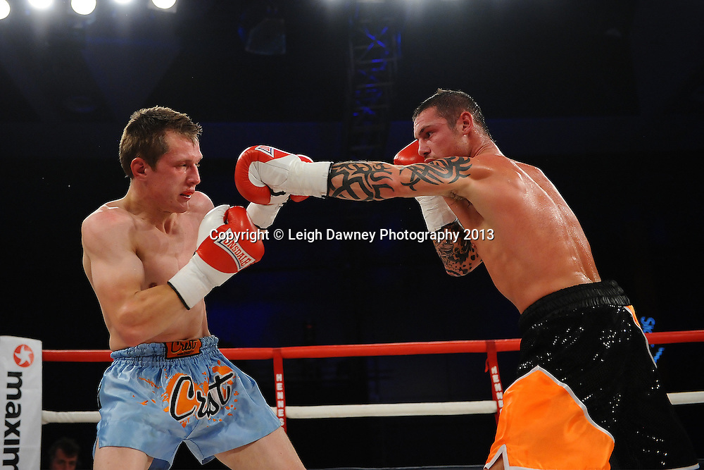 Garry Neale (black/orange shorts) boxing Simas Volosinas in a Light Welter weight contest. Glow, Bluewater, Kent, UK. Hennessy Sports © Leigh Dawney Photography 2013.