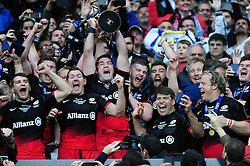 Brad Barritt of Saracens lifts the European Rugby Champions Cup trophy as his team celebrate victory - Mandatory byline: Patrick Khachfe/JMP - 07966 386802 - 14/05/2016 - RUGBY UNION - Grand Stade de Lyon - Lyon, France - Saracens v Racing 92 - European Rugby Champions Cup Final.