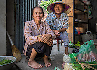 VIET HUNG, VIETNAM - CIRCA SEPTEMBER 2014:  Vietnamese women seating on a typical vegetable store on the streets of the Viet Hung village  in Vietnam