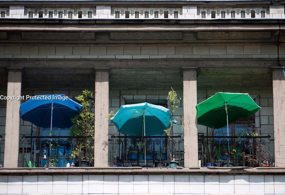 Summer parasols on balconies of old apartment buildings on Karl Marx Allee in Berlin Germany
