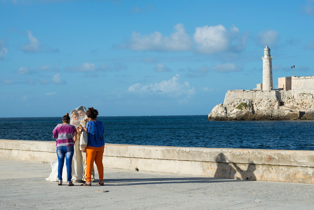 A photographer and an assistant stand with a Cuban bride and groom during a wedding photo shoot at the entrance to Havana Harbor in Havana, Cuba. Across the entrance is the lighthouse at Castillo de los Tres Santos Reyes Magnos del Morro.
