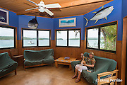 guest relaxes with cat in sitting room at Ika Lahi Fishing Lodge, Hunga Island, Vava'u, Kingdom of Tonga, South Pacific