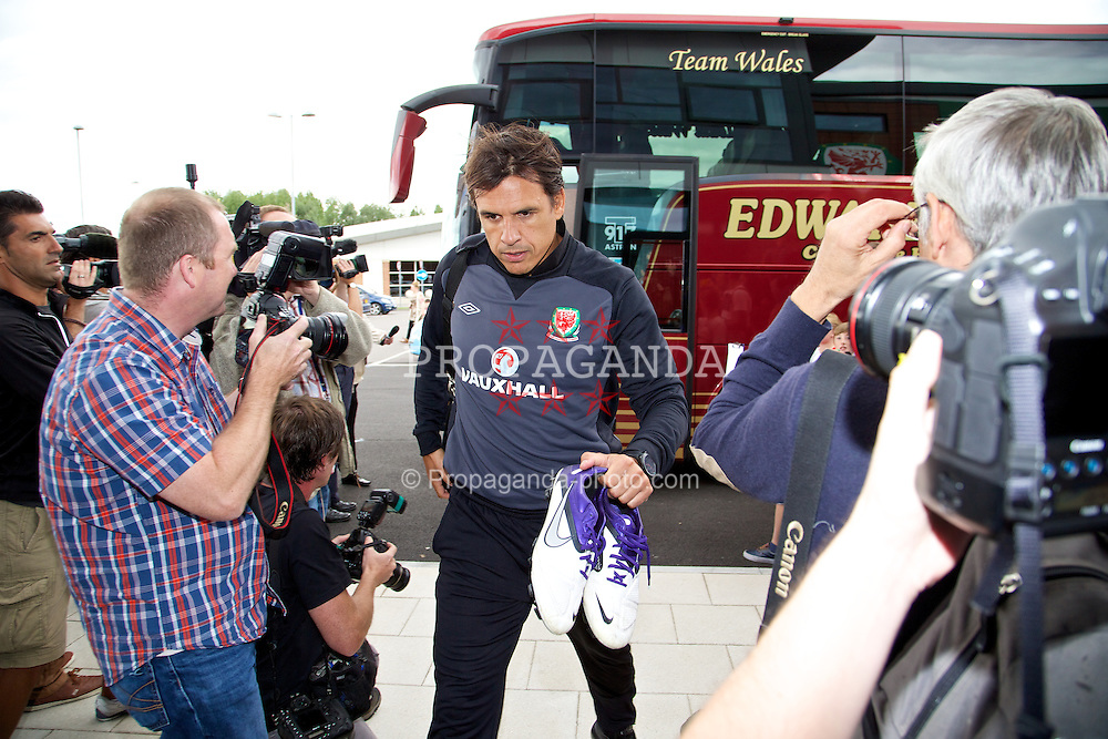 NEWPORT, WALES - Monday, August 12, 2013: Wales' manager Chris Coleman squeezes past photographers as he arrives for training at the FAW National Development Centre at Dragon Park ahead of the International friendly against the Republic of Ireland. (Pic by David Rawcliffe/Propaganda)