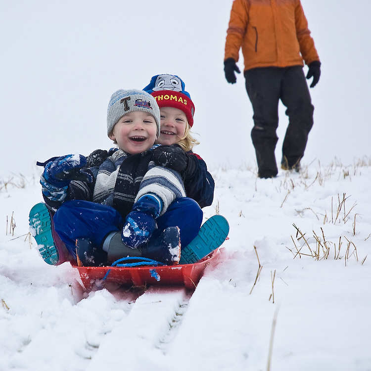 Children, boy and girl toddlers, enjoying the snow, sledging at Shap,Cumbria, England, UK