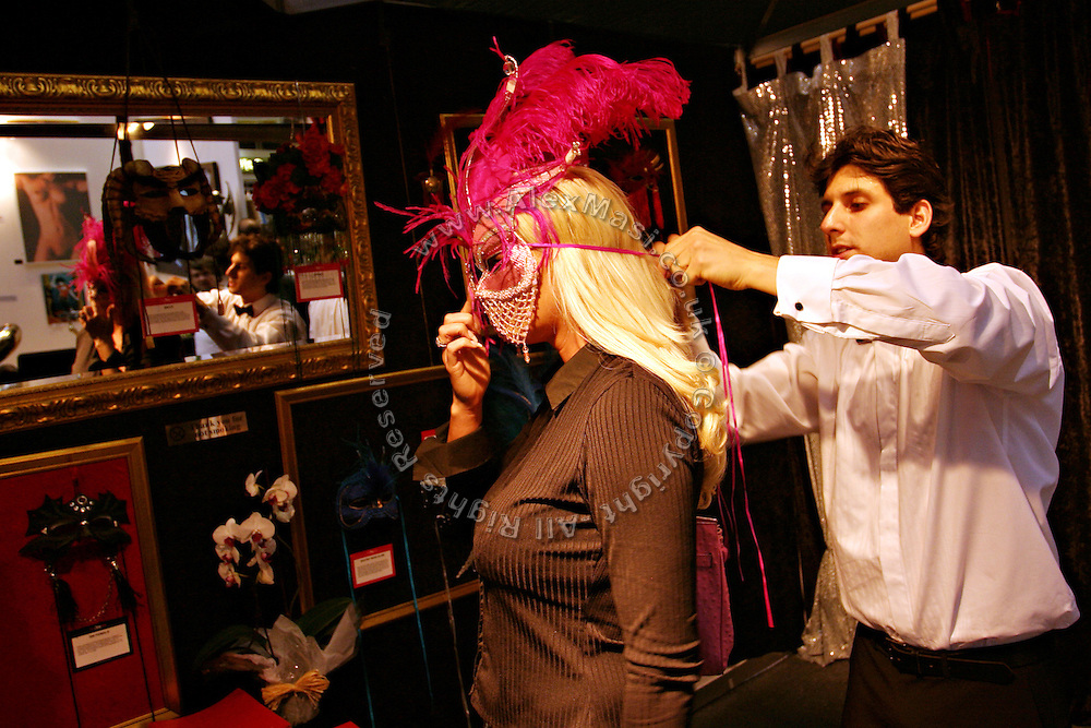 A woman is trying a fancy mask in one of the exhibitors' stands at the Erotica 2006 show in London, UK, on Friday, Nov. 17, 2006. Erotica is the world's largest adult lifestyle show. It attracts about 80,000 visitors every year with its over 150 retailer exhibitors, dazzling and decadent transvestite cabaret shows, fun foreplay seminars, beautiful lingerie collections, art and fetish demonstrations. **Italy Out**