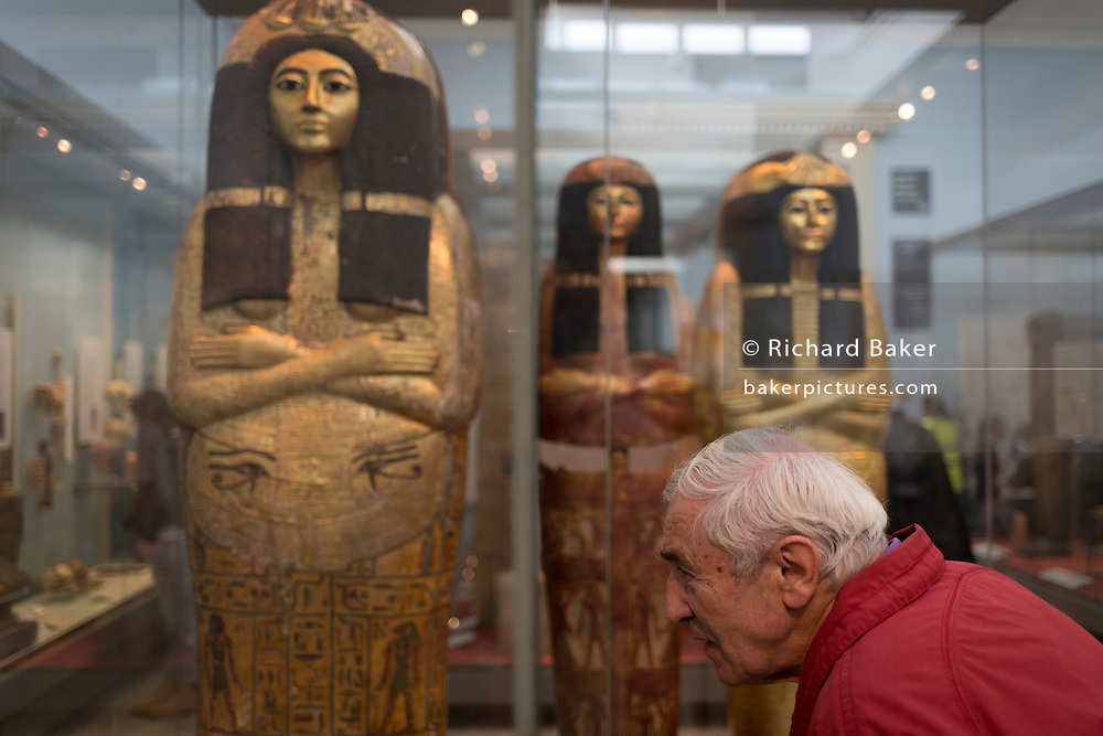 An elderly visitor inspects New Kingdom (1279-1213BC) Egyptian Mummies of Henutmehyt in the British Museum, on 28th February 2017, in London, England.