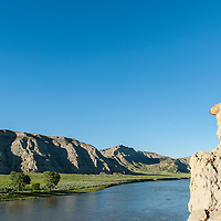 a hiker sits on a clif overlooking the wild and senic missouri river in the umrbnm, spring, montana