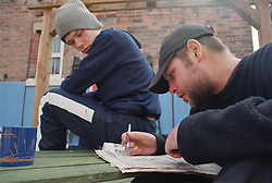 Two male residents sitting on bench in back garden of Young Persons' Resettlement hostel doing newspaper crossword,