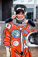 A young girl tries on a space suit outside the Space Museum. Yoichi is the home of Mohri Mamoru, Japan's first NASA astronaut who flew on the Endeavour in 1992. The space museum honours that flight and the NASA programme.