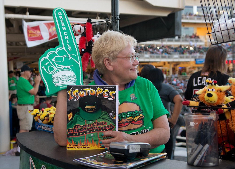 "mkb061617b/sports//Marla Brose --  Kim Moch watches the field while selling Albuquerque Green Chile Cheeseburgers foam fingers and programs for Friday night's baseball game against the Fresno Tacos, June 16, 2017, at Isotopes Park in Albuquerque, N.M. The  Albuquerque Green Chile Cheeseburgers took the field for one night only.  ""Food fight at the Grill,"" Moch said. (Marla Brose/Albuquerque Journal)"