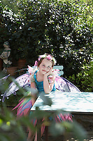 Portrait of young girl (5-6) in fairy costume sitting at garden table