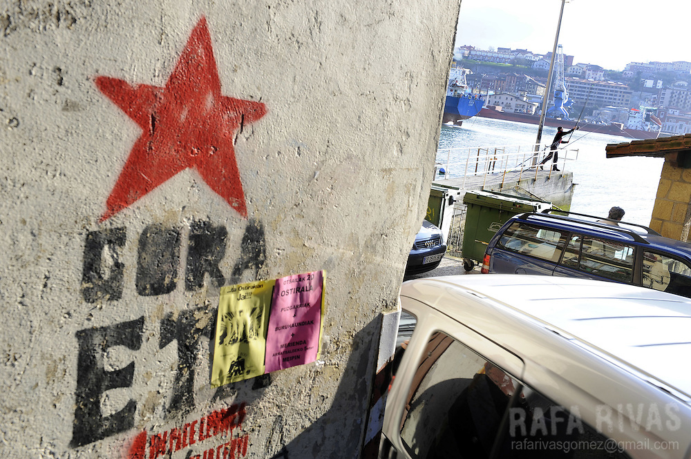 A man fishes at the port of the northern Spanish Basque village of Pasajes de San Pedro, close to a graffiti in favour of armed Basque group ETA, on February 18, 2009.