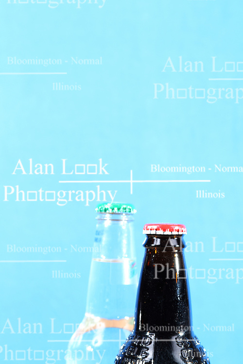 26 August 2015:   Studio - A pair of soda bottles, one dark, the other clear.  Both full with twist off caps still on the bottle