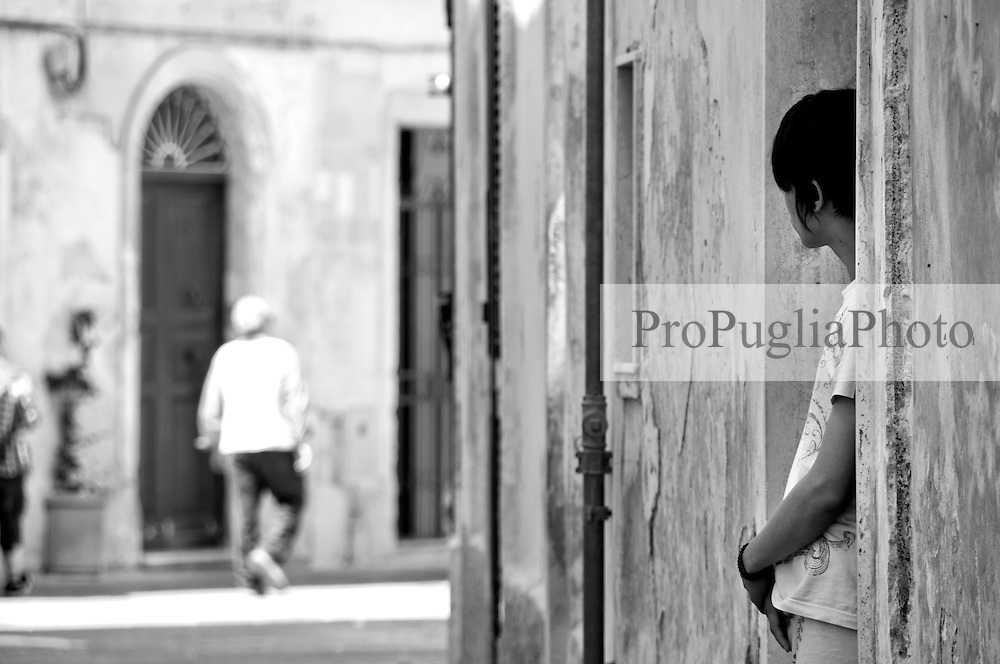 """Lecce - Zona Giravolte - L'integrazione ha trovato anche qui la propria """"casa"""". Un giovane cinese osserva il passaggio delle persone sulla strada."""