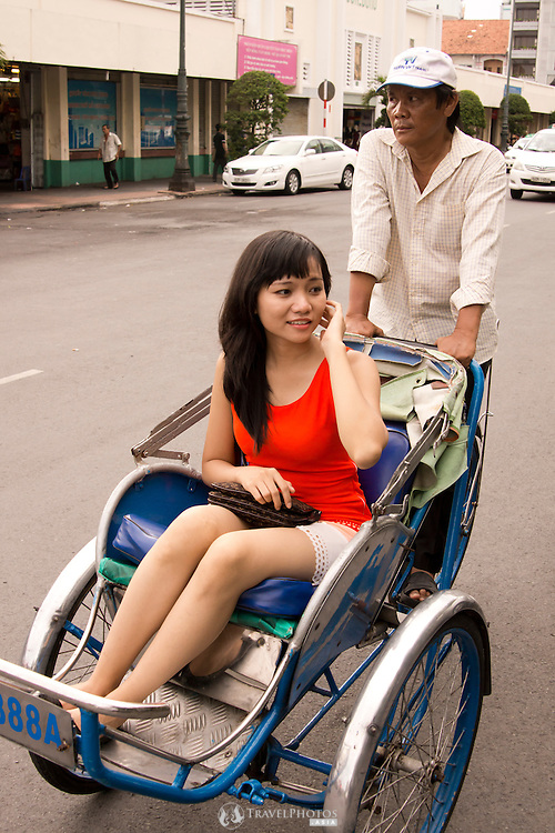 A young Vietnamese lady taking a ride on a Cyclo in Saigon, Vietnam.<br />