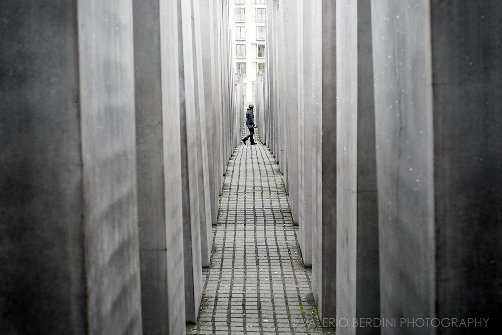 A person walks past the monoliths of the holocaust memorial in Berlin.