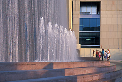Stock photo of a crowd standing in front of a flowing fountain on a sunny afternoon