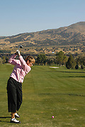 Idaho, Pocatello.  Woman tees off while golfing at Juniper Golf course.