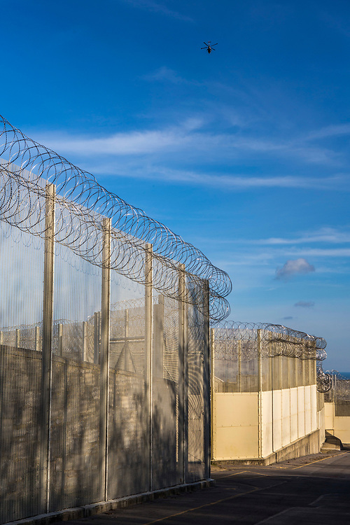A helicopter flying over security fencing inside HMP/YOI Portland, a resettlement prison with a capacity for 530 prisoners. Dorset, United Kingdom.