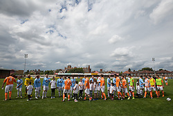 © Licensed to London News Pictures . 02/08/2015 . Droylsden Football Club , Manchester , UK . Players and mascots shake hands . Celebrity football match in aid of Once Upon a Smile and Debra , featuring teams of soap stars . Photo credit : Joel Goodman/LNP